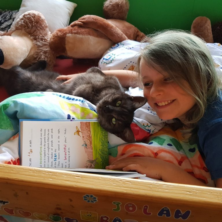 Jolan in bed with Ziggy cat, reading a story to the cat