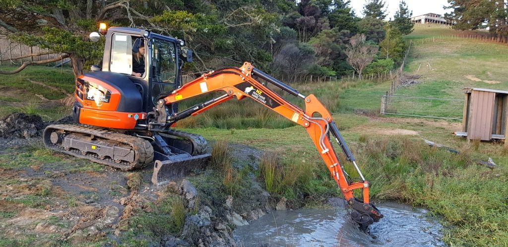 Excavator digging up silt from the stormwater pond
