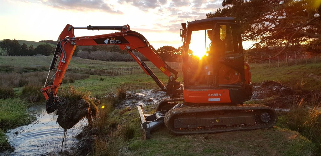 Picture of the excavator with Janus in it before the sunset in the background, sun shining through the cabin.