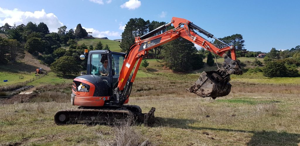 Picture of the excavator in the paddock with tatjana driving it, the site in the background