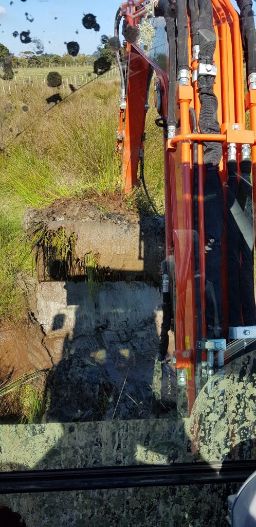 Photo taken from the excavator cabin, showing the bucket in front with soggy clay