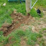 timber fence post with little trench and wire sticking out of the ground