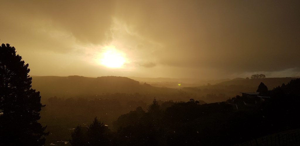 Layers of hills from almost black to yellow grey with the sun shining bright yellow through the clouds of rain