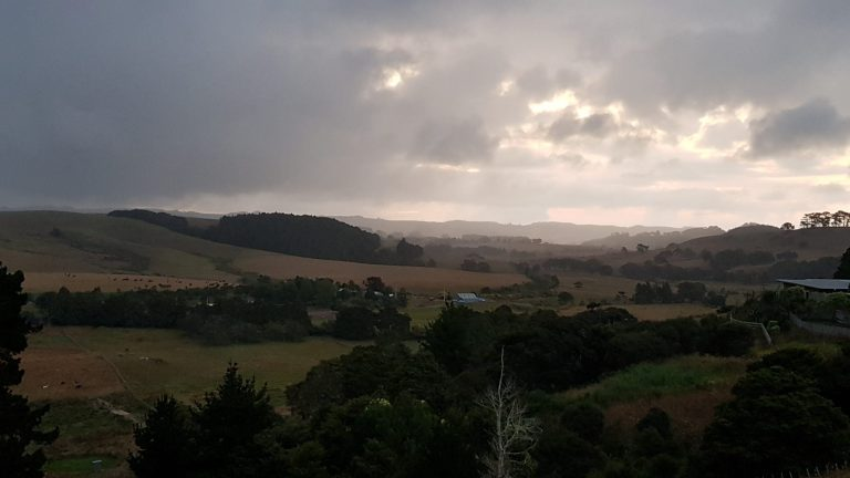 Look across the Kaipara valley with rainclouds in the background and diffuse light coming through the clouds.