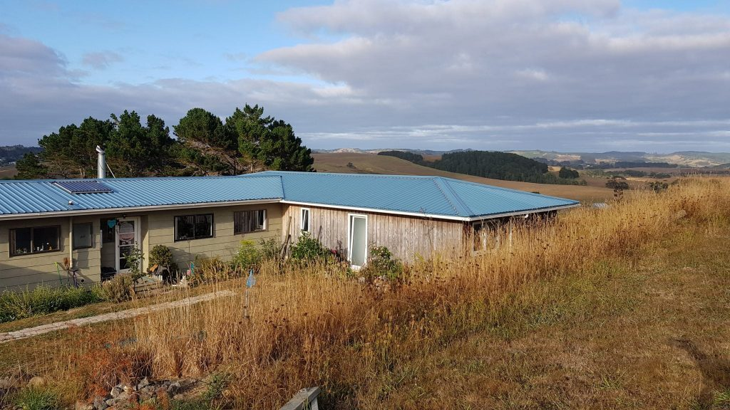 Picture from top of driveway looking down on house roof and across into the Kaipara valley with shades of brown and yellow landscape with a few green trees