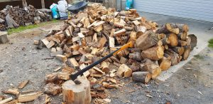 Piled up split firewood and some big chunks of wood in front of it with a chopping block