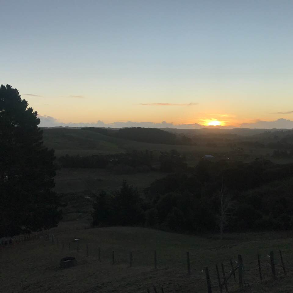 photo of the sun disappearing behind hills in the distance