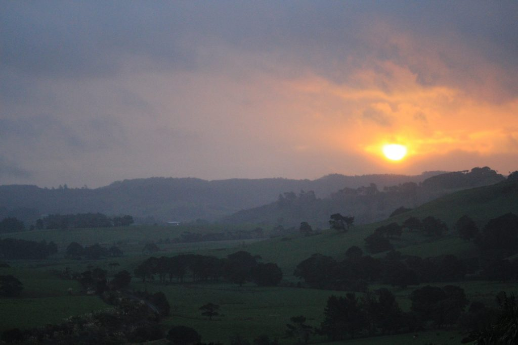 Rainy landscape in misty layers and some sun pushing through thick clouds orange in the background