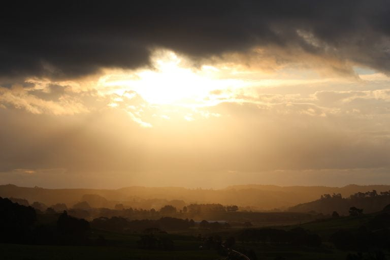 Valley with sun behind black rain clouds