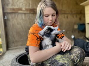 Child cradling a baby goat in her lap